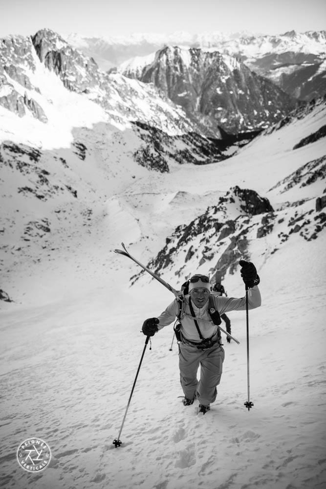 Laurent Dupré remonte un couloir, skis sur le dos