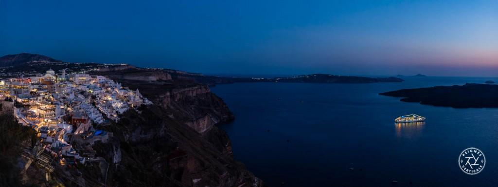 Panoramique sur le bateau de croisière qui passe la nuit au pied des falaises de Santorin