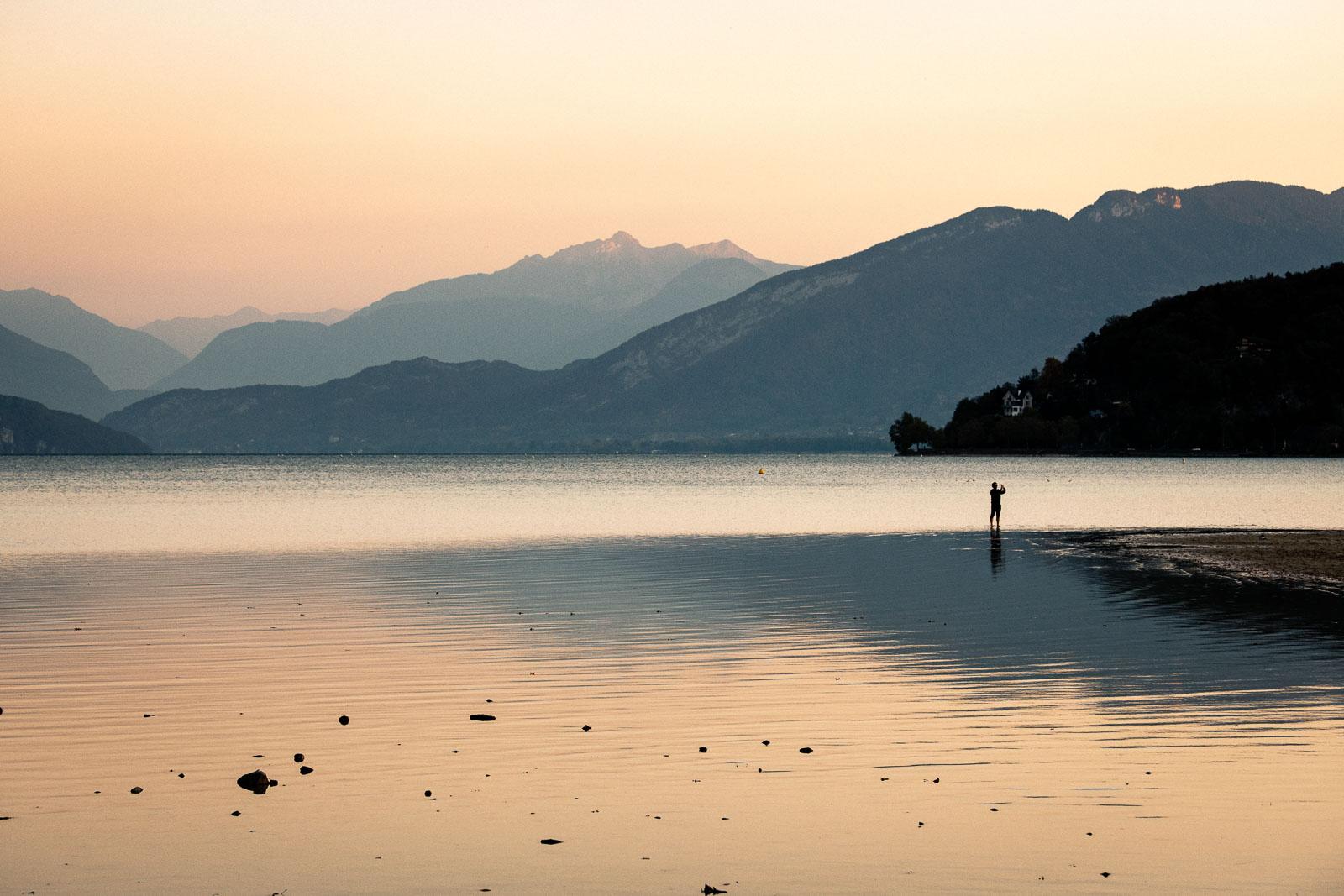 Passant photographiant le faible niveau d'eau du lac d'Annecy