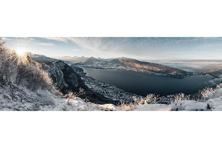 Timides rayons de soleil après une chute de neige depuis le Mont Veyrier, Annecy, France. Format panoramique.