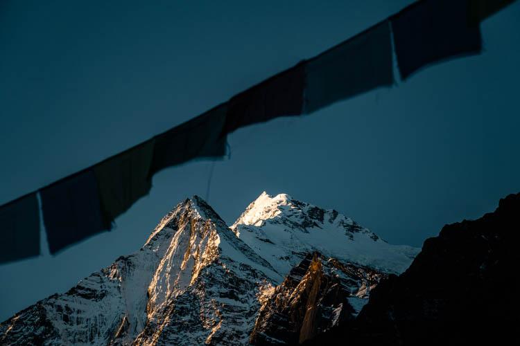 Drapeaux de prière sur fond de soleil couchant, Népal. Format paysage.