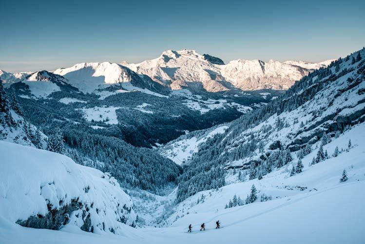 3 skieurs de randonnée font leur trace devant la Tournette qui s'illumine, France. Format paysage.