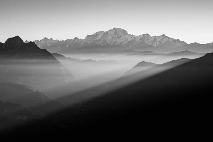 Lumière filtrée sur les vallées alpines face au Mont-Blanc, France. Format paysage.
