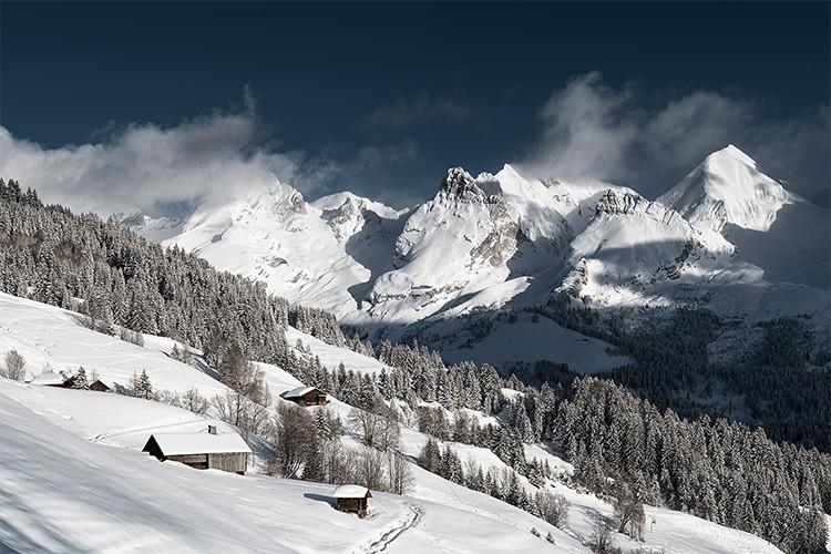 Vue depuis le Grand Bornand sur les combes des Aravis enneigées, France. Format paysage.