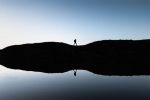 Randonneur se réflétant dans un lac de montagne, France. Format paysage.
