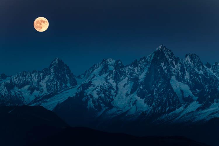 La pleine lune orangée surveille les sommets au Nord du Massif du Mont Blanc , France.