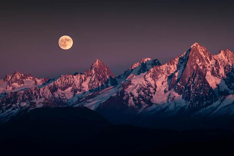 La pleine lune se lève un soir de novembre sur les sommets au Nord du Massif du Mont Blanc, France. Format paysage.