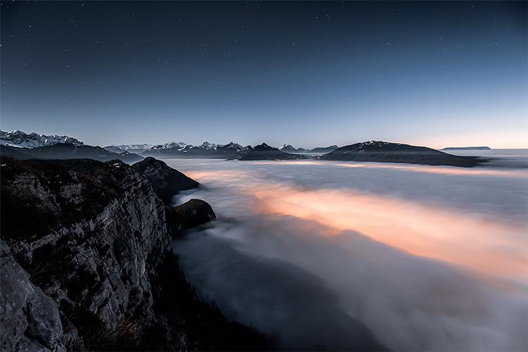 Mer de nuages et nuit étoilée depuis le Mont Veyrier, au-dessus du Lac d'Annecy, France. Format paysage.