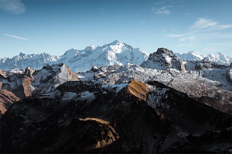 Chute de neige automnale sur les Aravis et la Pointe Percée surveillés par le Mont Blanc, France. Format paysage.